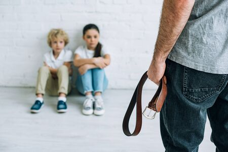 cropped view of abusive father holding belt and sad kids sitting on floor Stock Photo