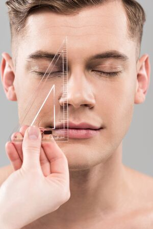 Cropped view of plastic surgeon measuring face with ruler isolated on grey background