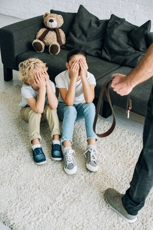 partial view of father with belt and upset kids sitting on floor