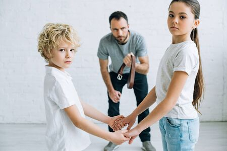 abusive father holding belt and children holding hands at home Stock Photo