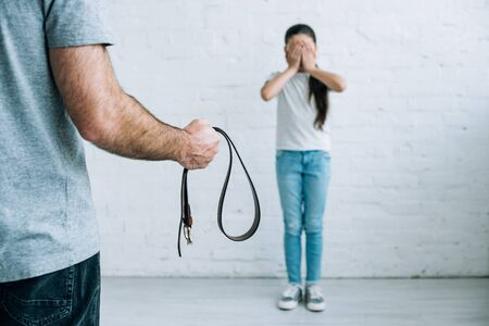 Partial view of abusive father holding belt and scared daughter at home