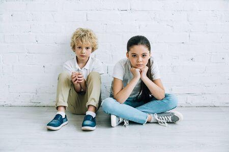 Sœur et frère bouleversés assis sur le sol à la maison Banque d'images