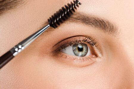 Cropped view of woman holding eyebrow brush near eyebrow Stock fotó