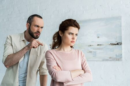 handsome man pointing with finger at upset woman with crossed arms Stock Photo
