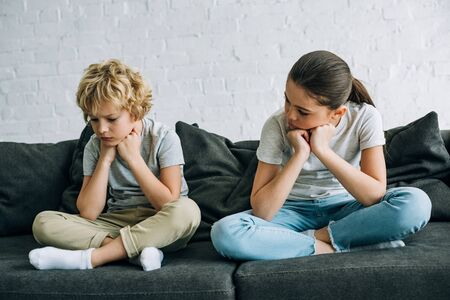 Two sad kids sitting on sofa in living room Archivio Fotografico - 124713100