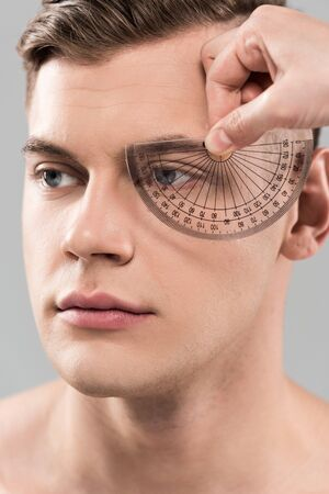 Partial view of plastic surgeon measuring face with protractor isolated on grey background