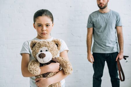 partial view of abusive father with belt and sad daughter holding teddy bear