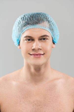 Front view of smiling naked young man in medical cap isolated on grey background