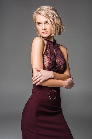 Hermosa chica rubia con estilo en ropa burdeos posando aislada sobre fondo gris