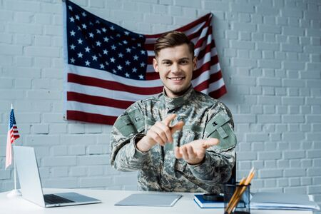 happy man in military uniform pointing with finger near laptop