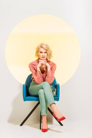Beautiful stylish girl in colorful clothes looking at camera and sitting in armchair on white background with yellow circle