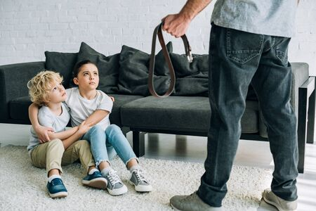 Partial view of father with belt and upset kids sitting on floor Stockfoto