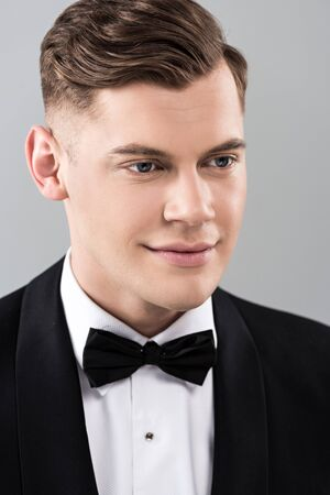 Smiling young man in formal wear with bow tie isolated on grey background