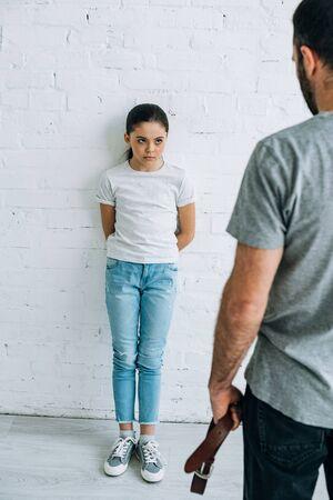 Vue recadrée du père tenant la ceinture et de la fille ayant un conflit