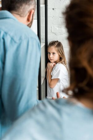 selective focus of frustrated kid looking at father at home Stock Photo