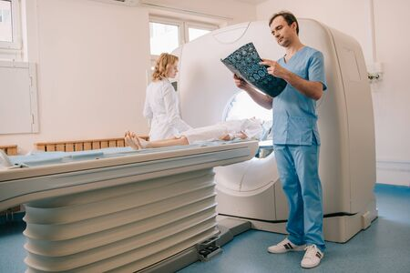 Attentive doctor looking at tomography diagnosis while radiologist operating ct scanner during patients diagnostics
