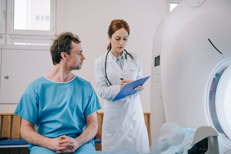 Man sitting on ct scan bed near attentive radiologist writing on clipboard