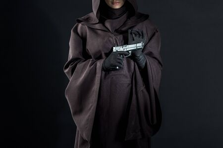 Cropped view of woman in death costume holding gun on black background Banco de Imagens