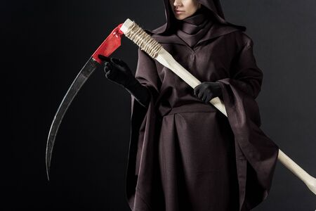 Cropped view of woman in death costume holding scythe on black background