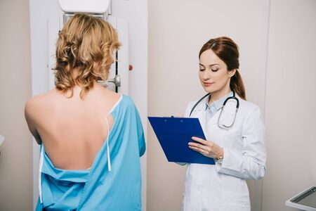 Beautiful young doctor looking at clipboard while standing near patient during mammography test on x-ray machine Archivio Fotografico