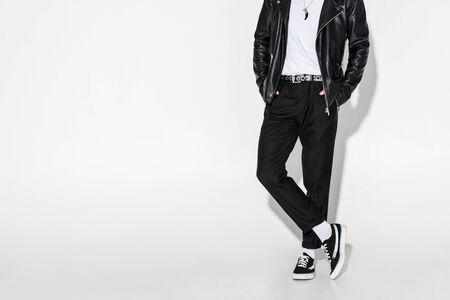Cropped view of man in leather jacket standing with crossed legs on white background Stock Photo