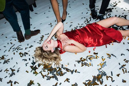 Attractive and drunk blonde girl in red dress lying on floor with confetti near friends 스톡 콘텐츠