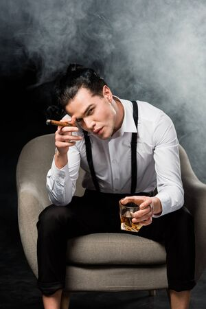 Handsome man looking at camera and holding glass of whiskey and cigar on black background with smoke