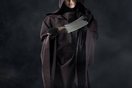 Partial view of woman in death costume holding cleaver on black background