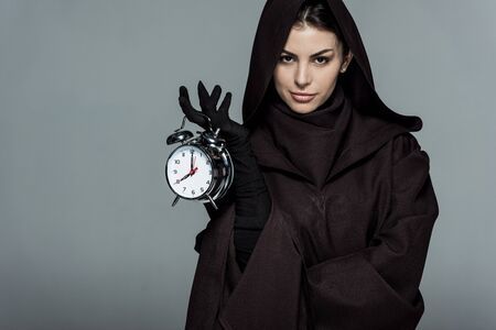 Woman in death costume holding alarm clock isolated on grey background Banco de Imagens