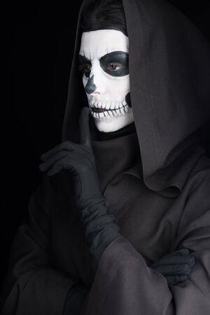 Woman with skull makeup showing hush sign isolated on black background