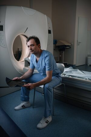Serious radiologist holding x-ray diagnosis while sitting near computed tomography scanner and looking at camera