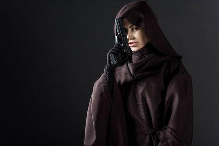 Woman in death costume holding gun isolated on black background Archivio Fotografico - 125073176