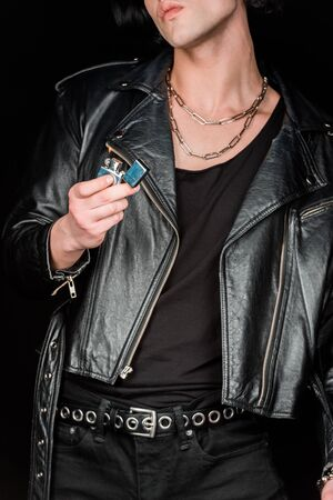Cropped view of man holding lighter with burning fire isolated on black background