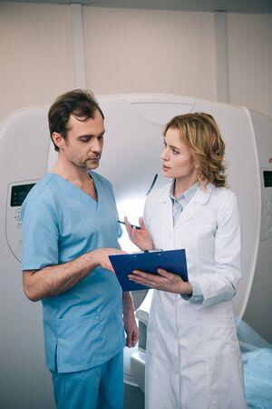 Two serious radiographers talking while examining radiology diagnosis