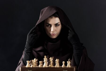 Front view of woman in death costume with chess isolated on black background Archivio Fotografico - 125073214