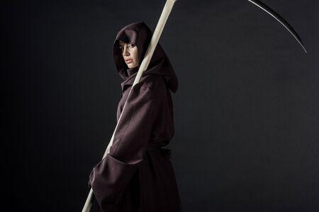Frau im Todeskostüm mit Sense und Blick in die Kamera isoliert auf schwarzem Hintergrund
