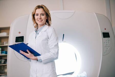 Radiólogos sonrientes que escriben en el portapapeles mientras están de pie cerca del escáner de tomografía computarizada