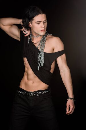 Handsome man with chains around neck touching tank top while standing isolated on black background