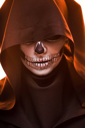 Woman with skull makeup in black death costume Imagens