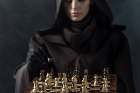 Cropped view of woman in death costume playing chess on black background