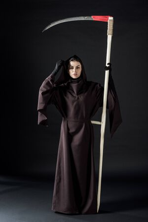 Full length view of woman in death costume holding scythe on black background
