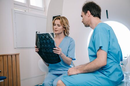 Attentive radiographer looking at x-ray diagnosis near patient sitting on ct scanner bed Zdjęcie Seryjne