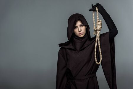Woman in death costume holding hanging noose isolated on grey background