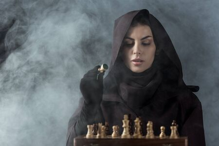 Woman in death costume playing chess in smoke on black background