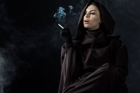 Woman in death costume smoking cigarette on black background