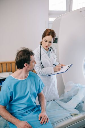 Attentive doctor writing on clipboard while standing near patient sitting on ct scanner bed