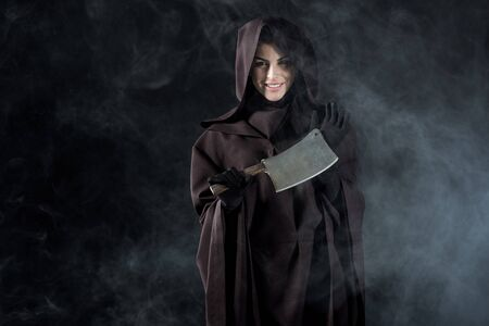 Woman in death costume holding cleaver in smoke on black background Imagens