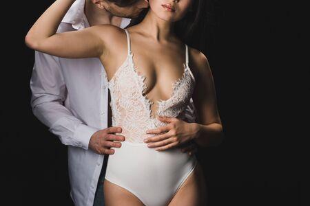 Vista recortada del joven en camisa blanca besando y abrazando a la novia asiática en lencería blanca aislada sobre fondo negro