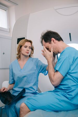 Upset man covering face with hands while sitting near radiologist in hospital