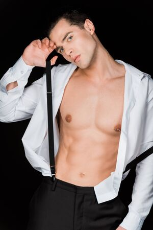 Handsome man touching suspenders and standing isolated on black background